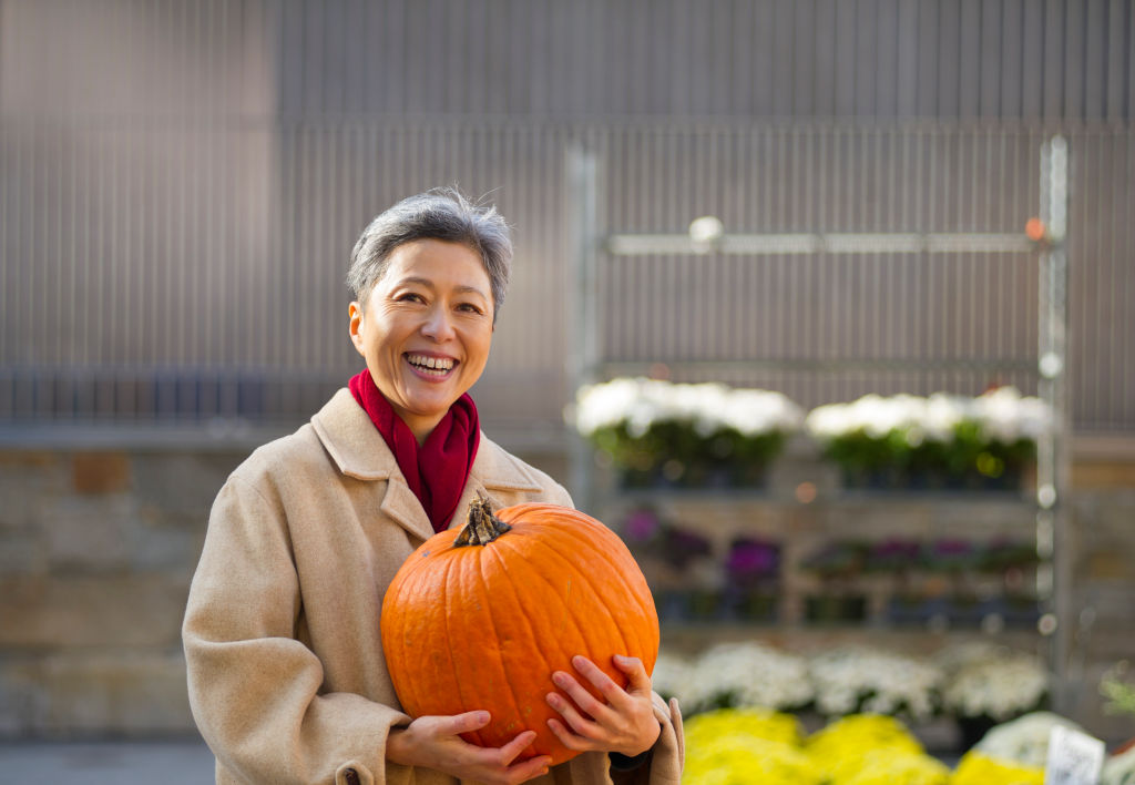 A woman smiles while holding a large, orange pumpkin.