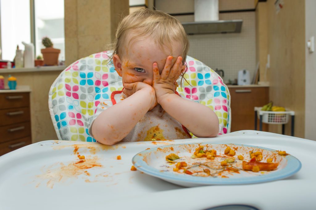 A baby sitting in a highchair is covered with tomato sauce.