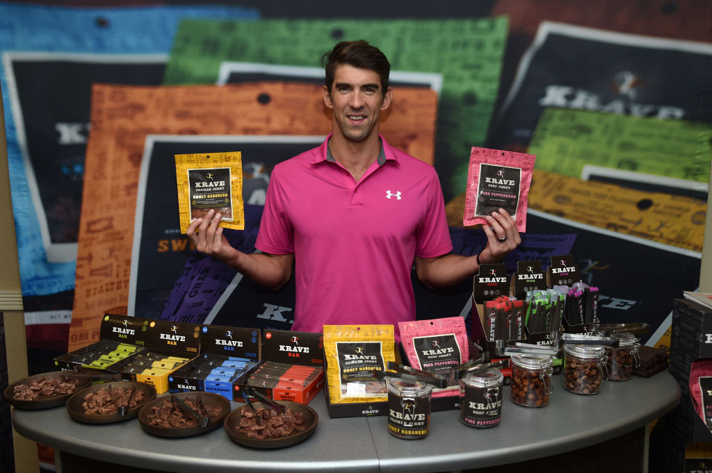 Michael Phelps holds up to bags of KRAVE jerky.