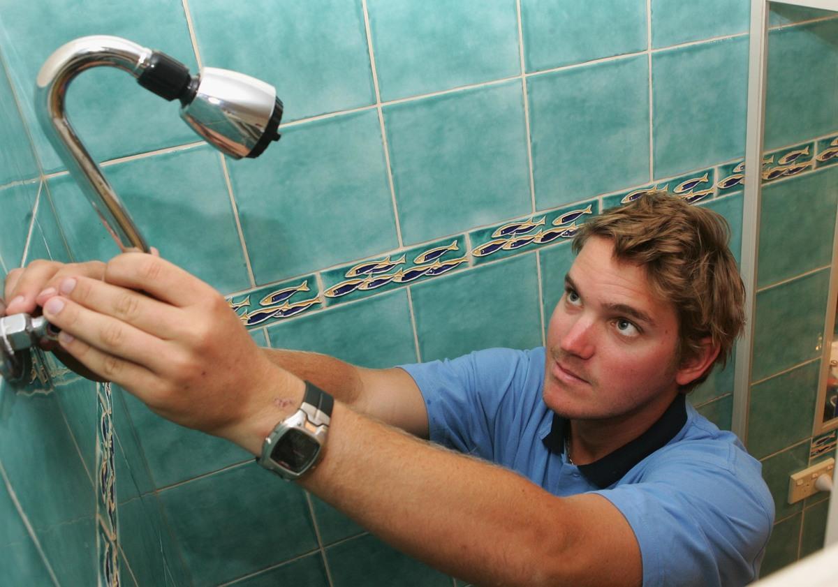 A tradesman intalls a water saving showerhead.
