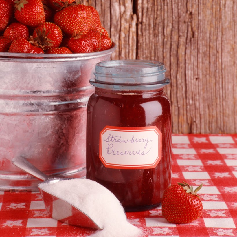 A jar of strawberry jelly sits in front of a basket of strawberries and a scooper of suger.