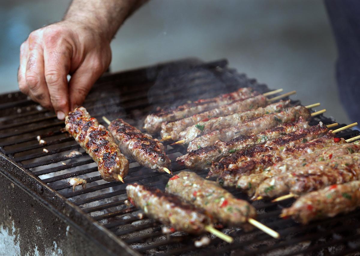 Man grills lamb kebabs.