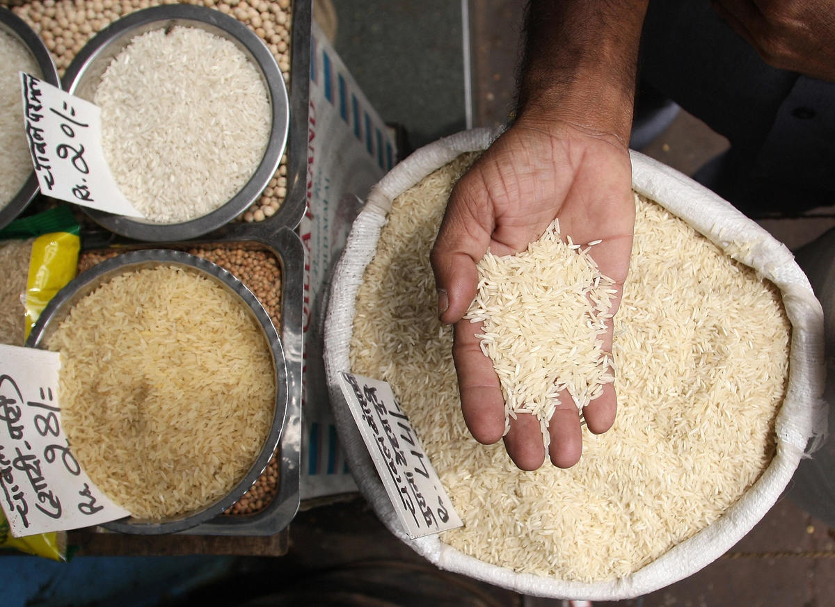 An Indian customer checks out different varieties of rice at a wholesale market.