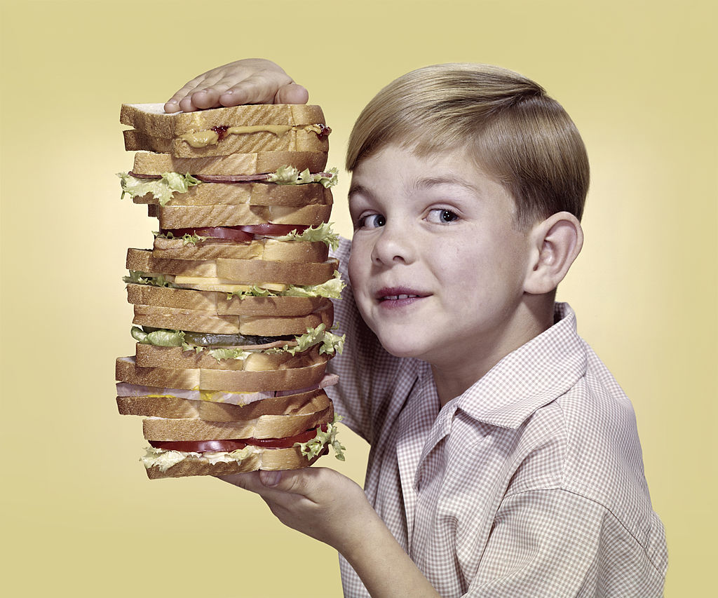 A boy holds up a stack of about seven sadwhiches on top of one another.