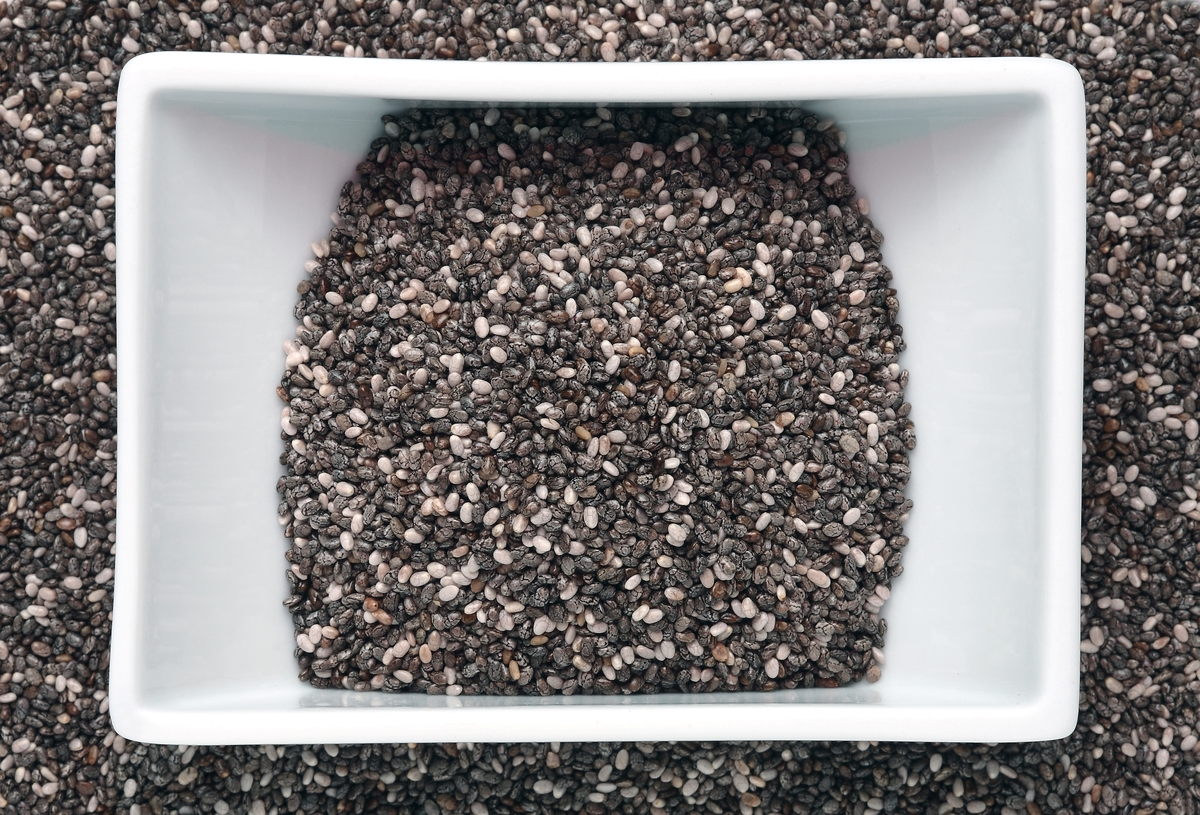 A sqaure-shaped bowl of chia seeds rests on more chia seeds.