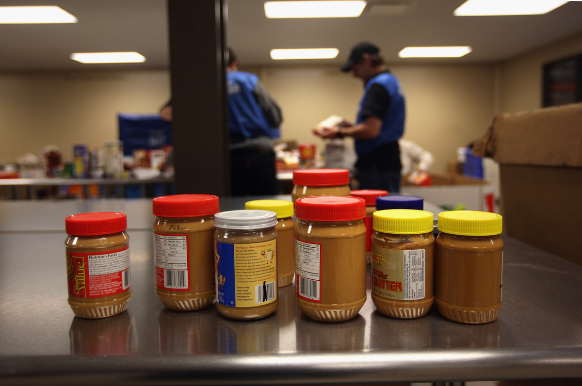 Donated jars of peanut butter are set on a table to be checked before redistributing.