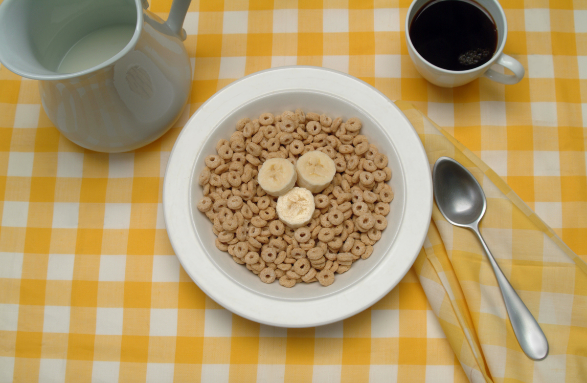 On a table, there's a bowl of breakfast cereal (and banana slices), a cup of coffee, and a pitcher of milk.