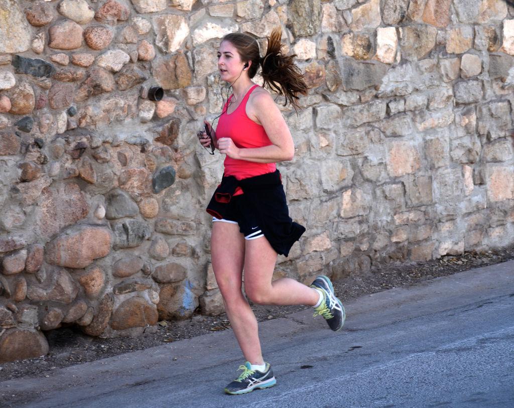 A woman jogs next to a stone wall.