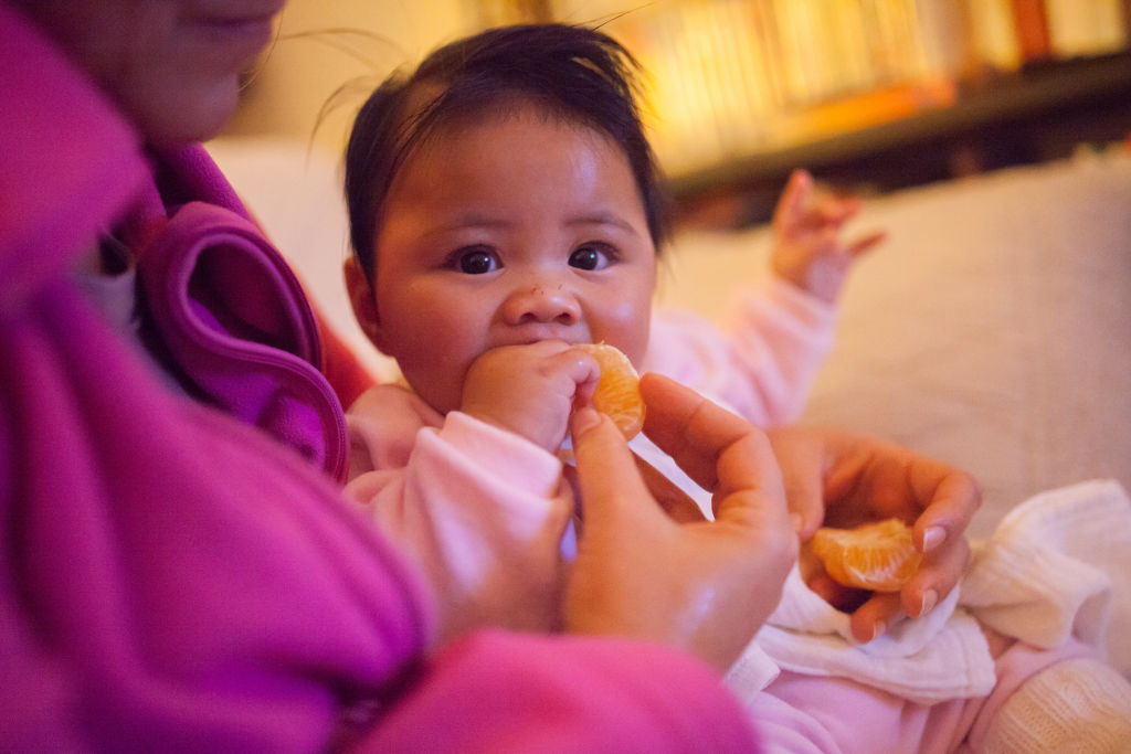 A mother feeds her baby orange slices.