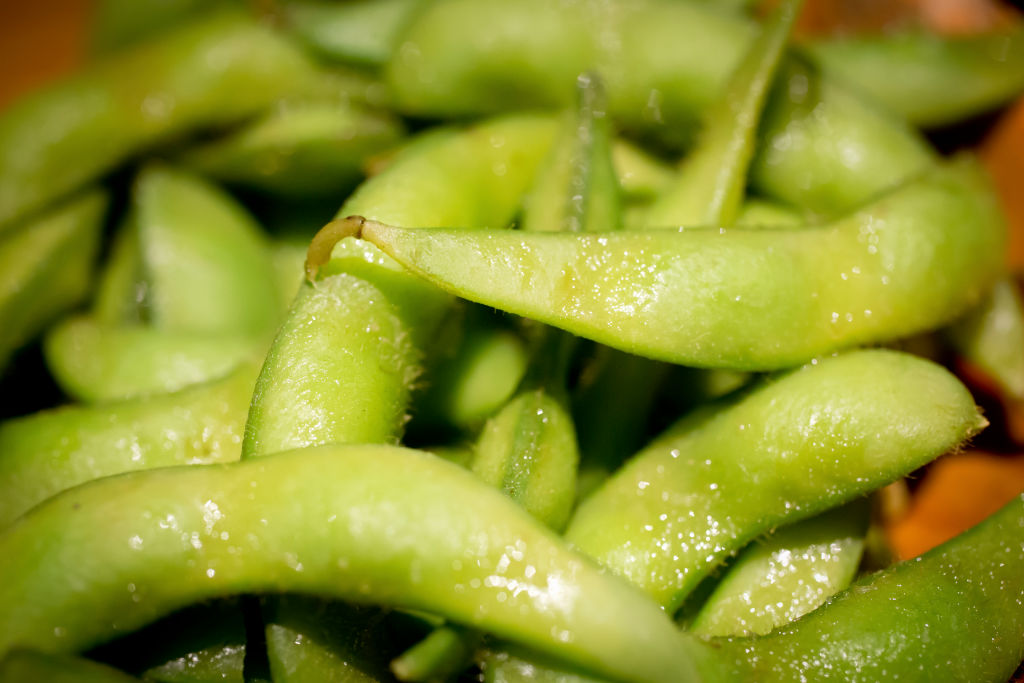 A closeup shows a pile of steamed edamame.