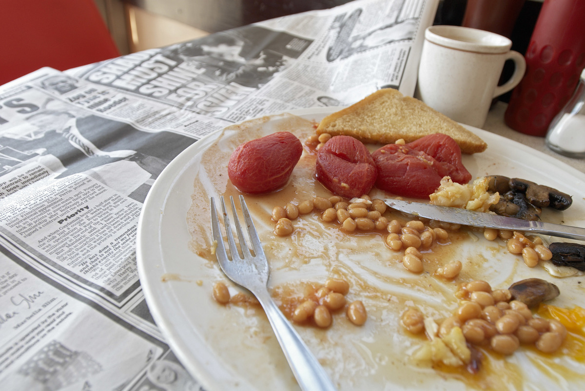 Refried beans are on a breakfast plate on a cafe table.