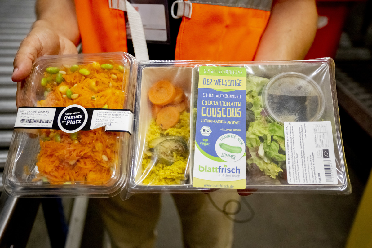 Employee holds two ready made salads, 'carrot & apple' and 'cocktail tomato couscous' in a cold storage.