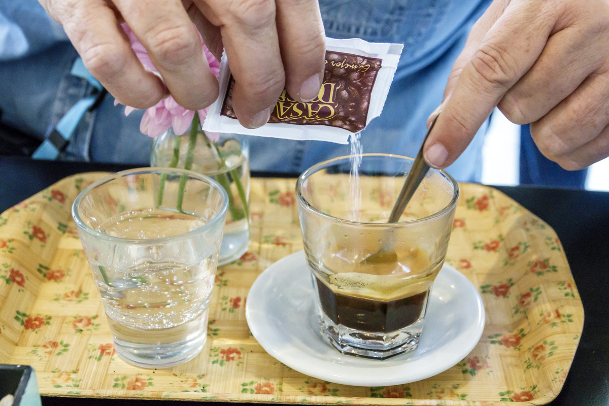 Person pours sugar into an espresso coffee.