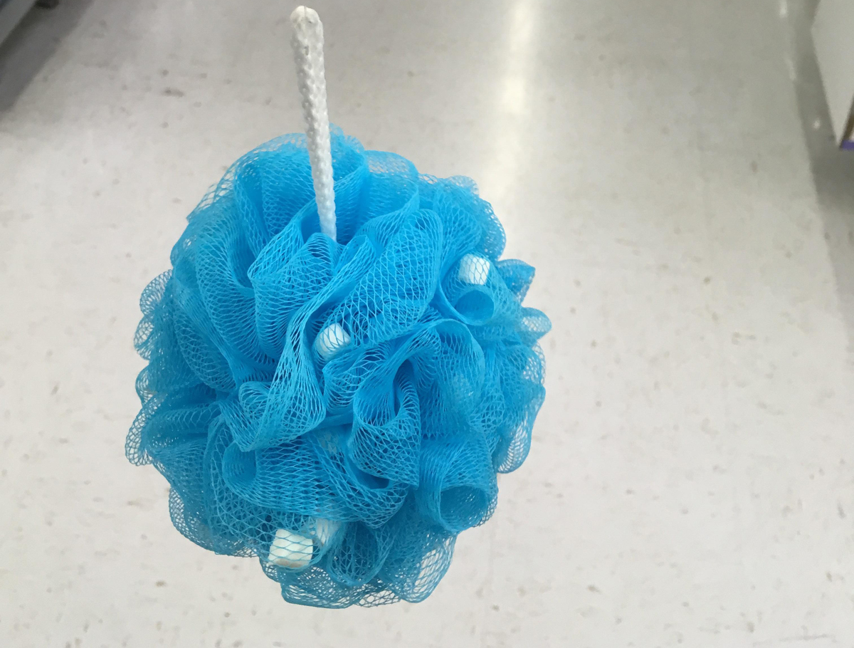 A blue loofah with soap beads inside of it is inside of a store.