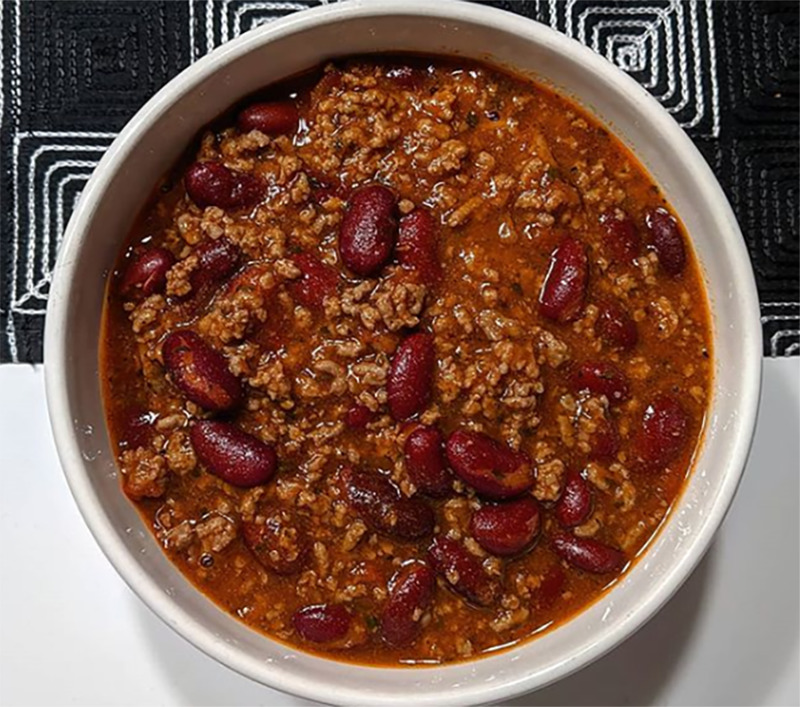 A bowl of chili is photographed from above.