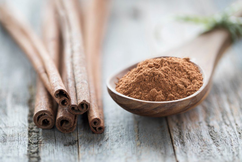 Cinnamon sticks rest next to a wooden spoon full of powdered cinnamon.