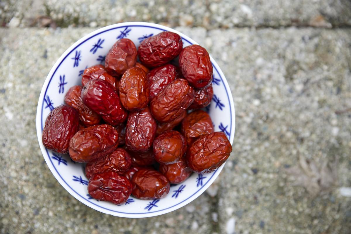 Red dried fruit sits on a white and blue plate.