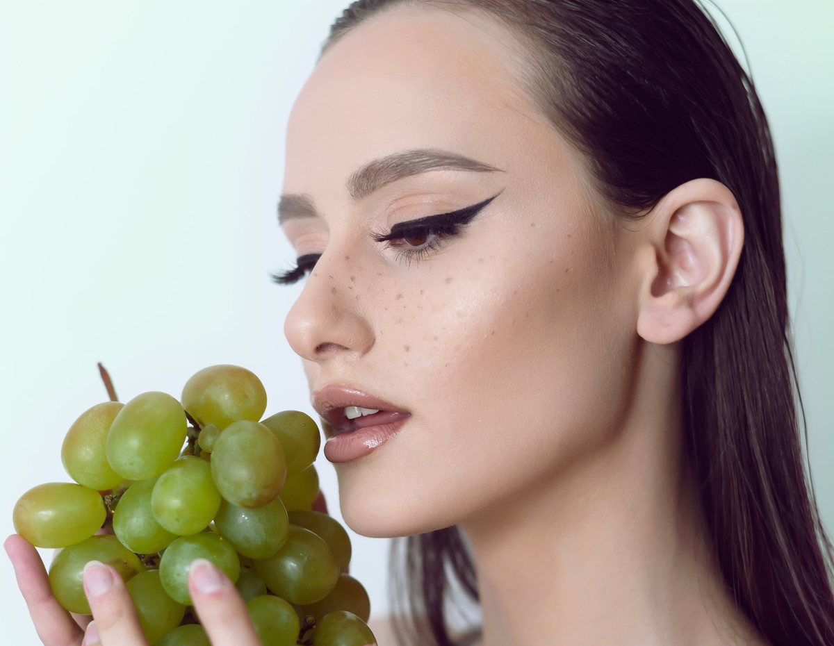 Woman holds green grapes to eat.