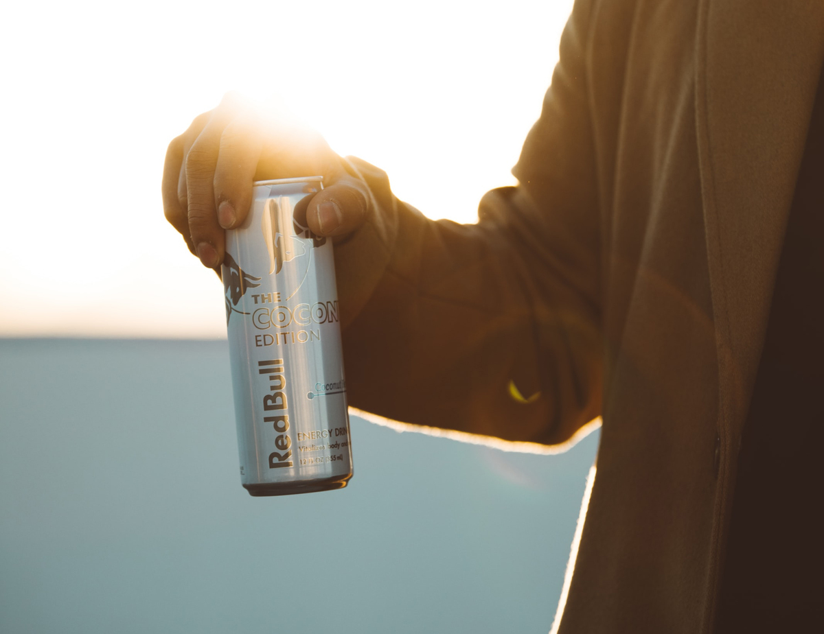 A man holds a can of Red Bull against the sunlight.