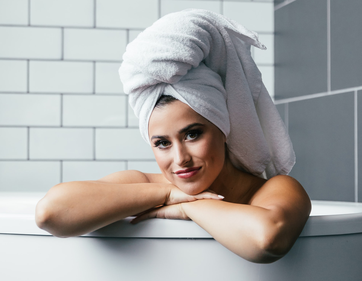 A woman with hair wrapped in a towel smiles as she sits in the bathtub.