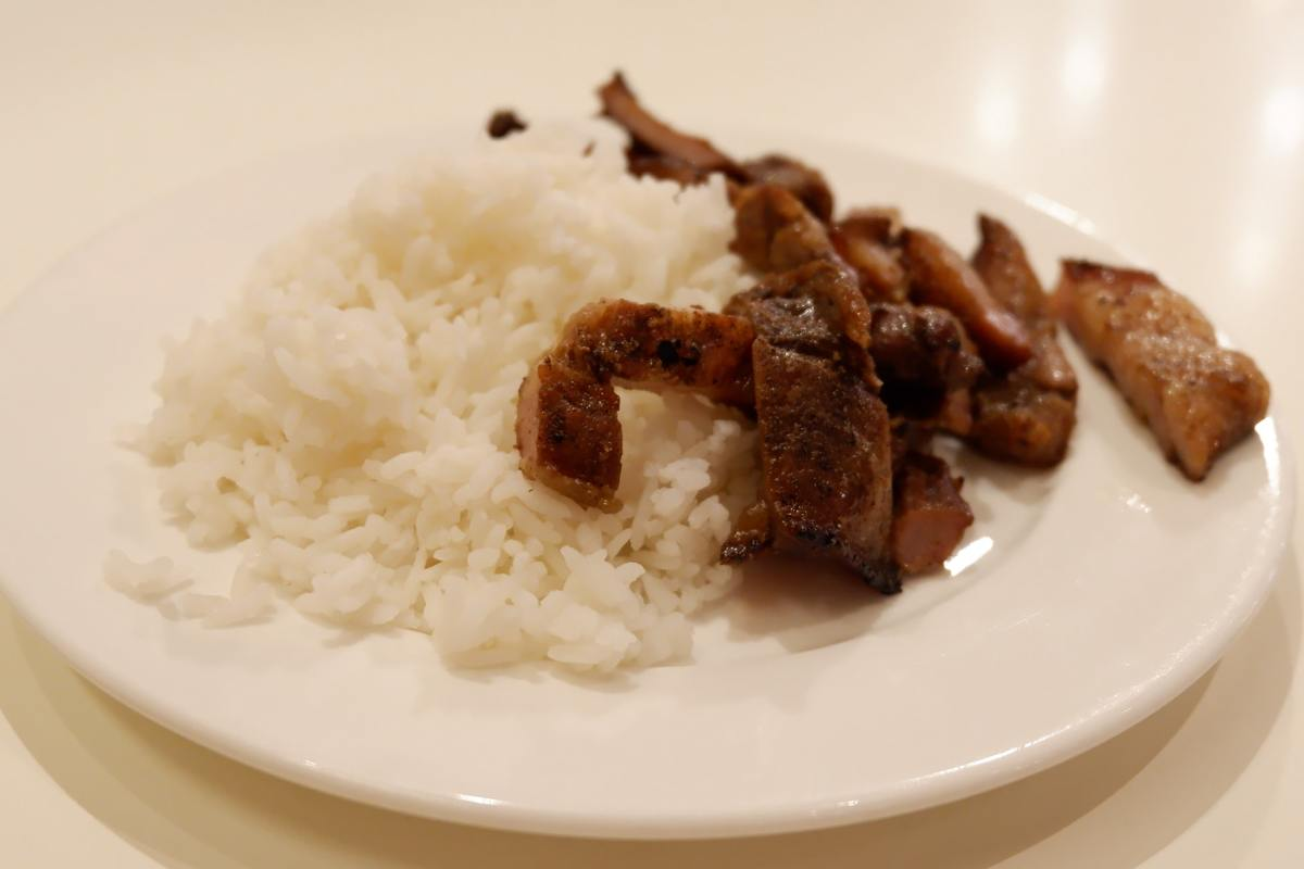 A plate holds white rice and pork.