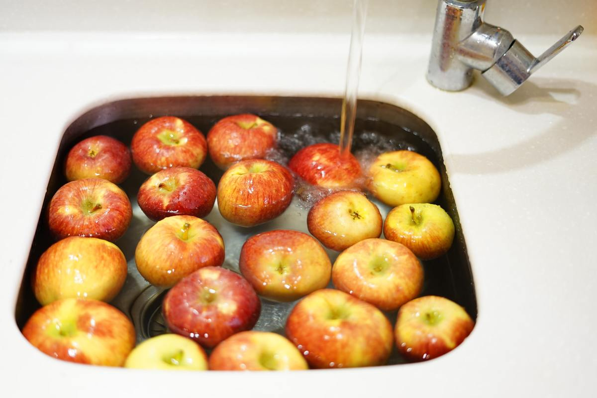 Red apples are washed in a sink full of water.