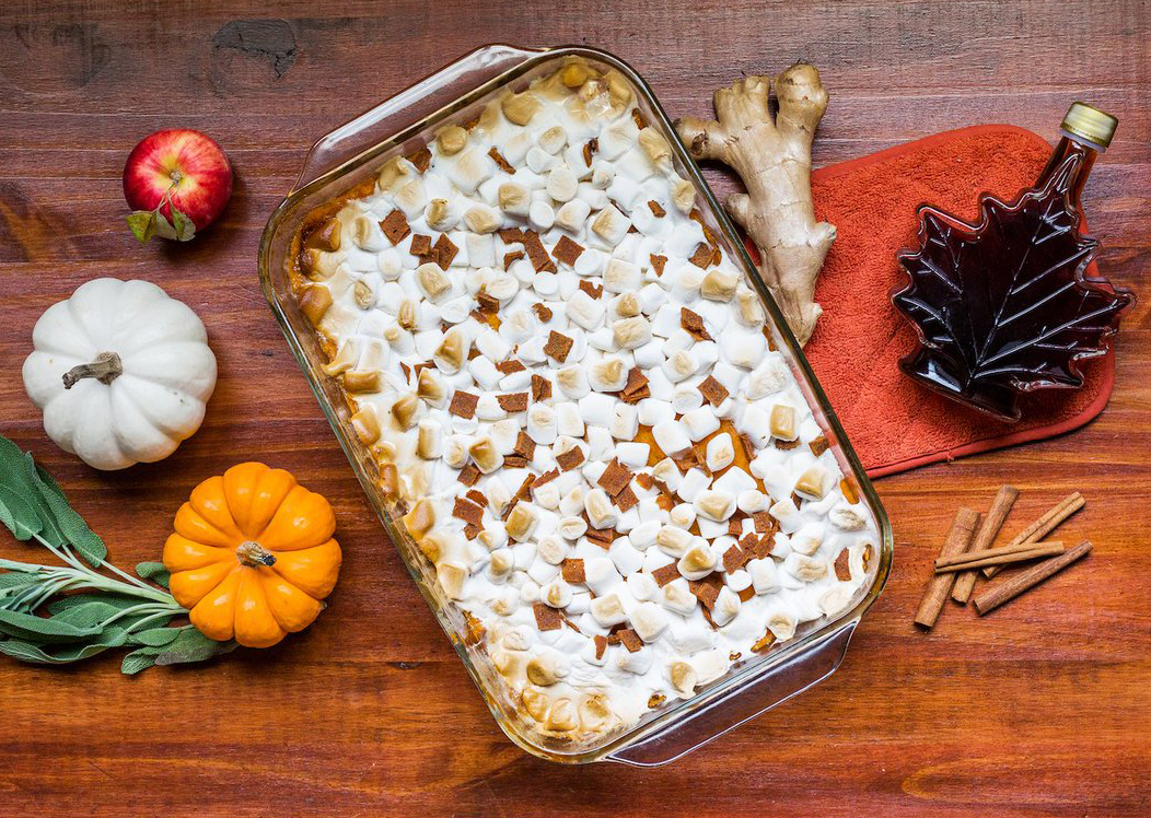 A pan of sweet potato casserole sits on a table with Thanksgiving decorations.