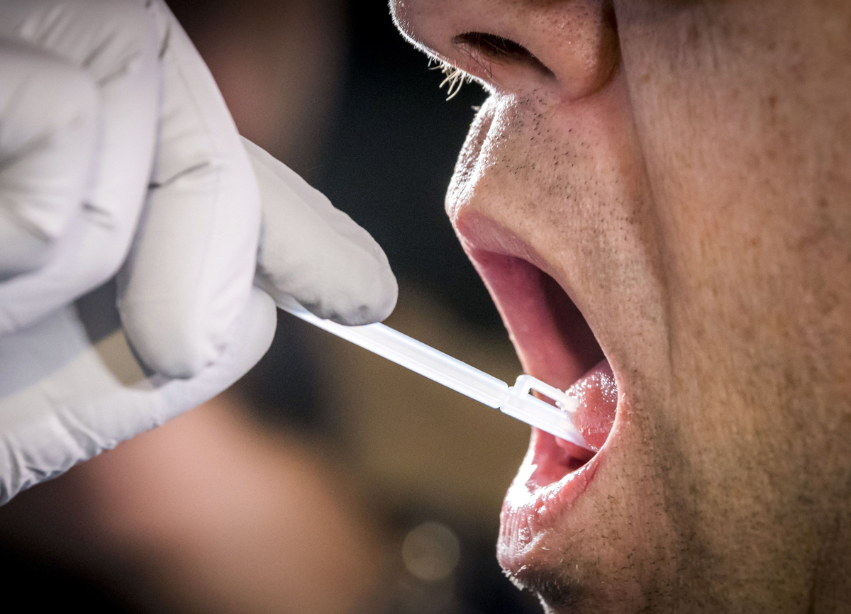 A DNA sample is taken by swabbing the patient's tongue.