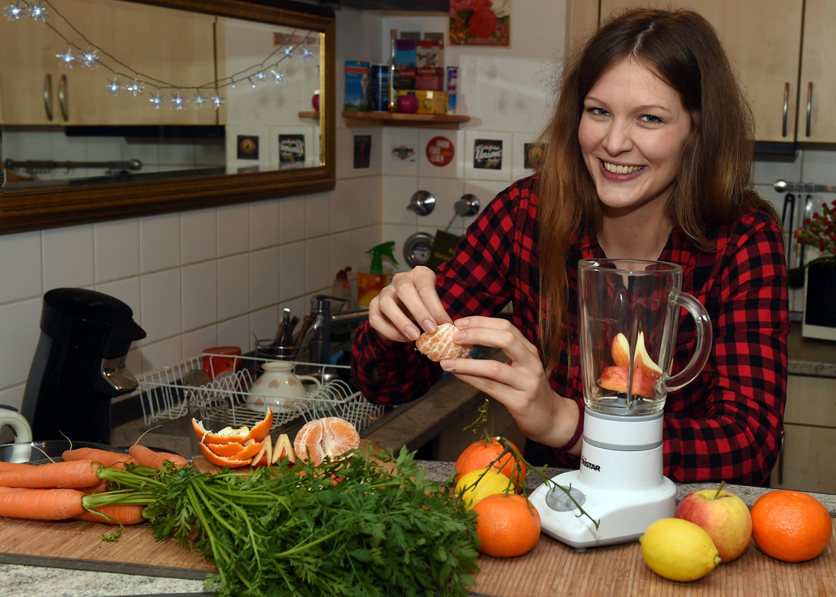 A young woman prepares a smoothie from fresh fruit and vegetables.