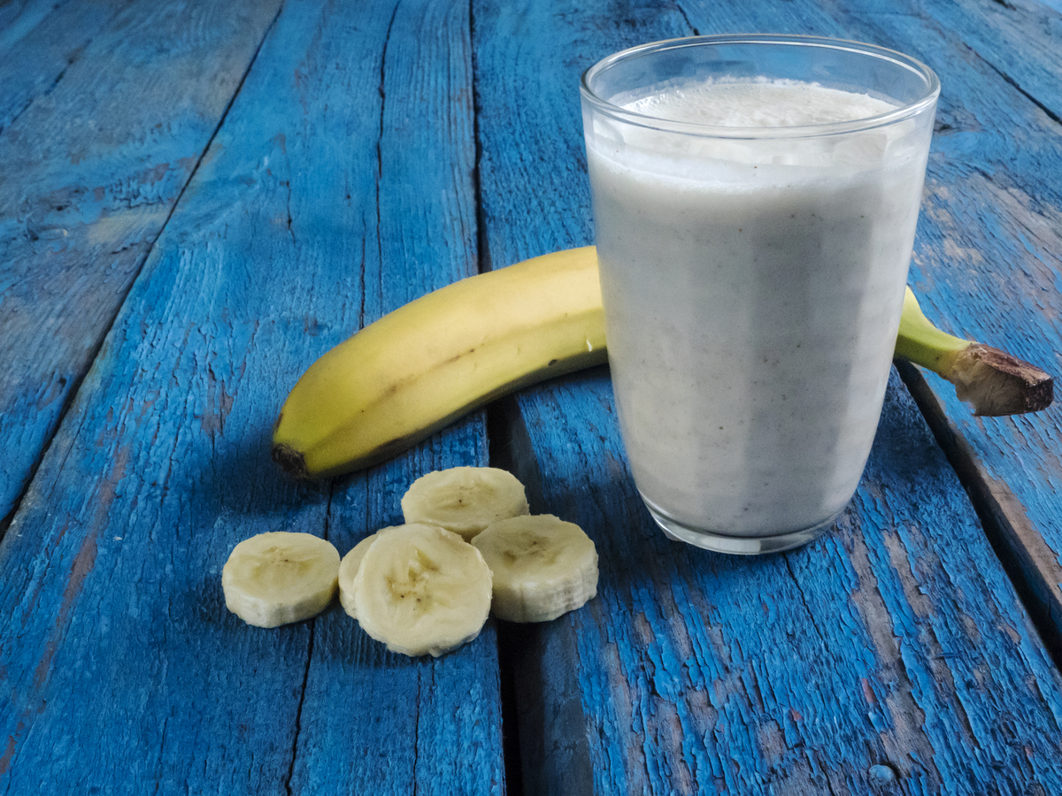A banana and banana smoothie lay on a blue wooden table.