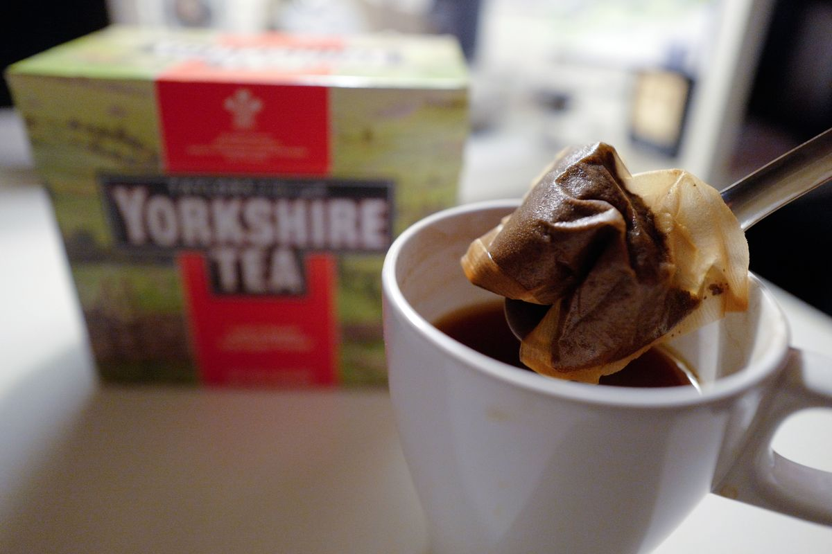 A man makes a cup of tea with a Yorkshire Tea teabag with a box of tea in the background.