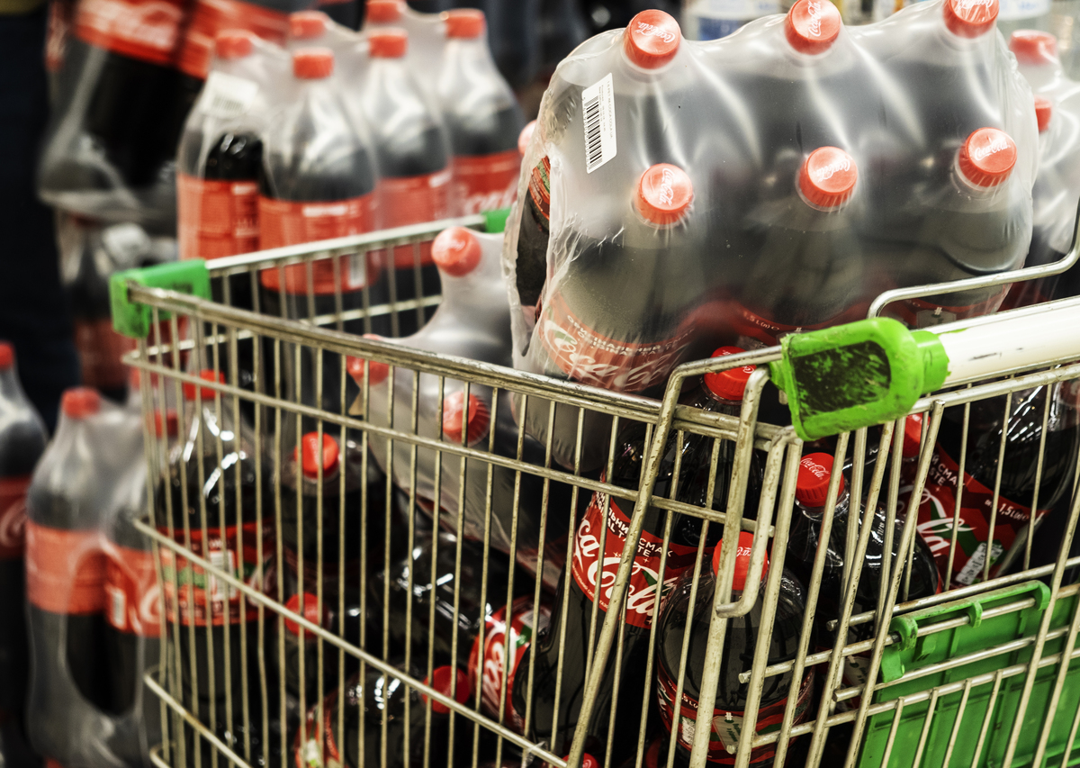 A cart loaded with lots of plastic Coca-Cola bottles seen at a supermarket.