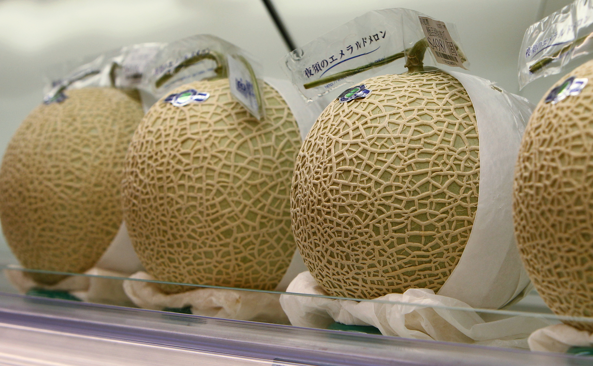Whole honeydew stands on display in Japan.