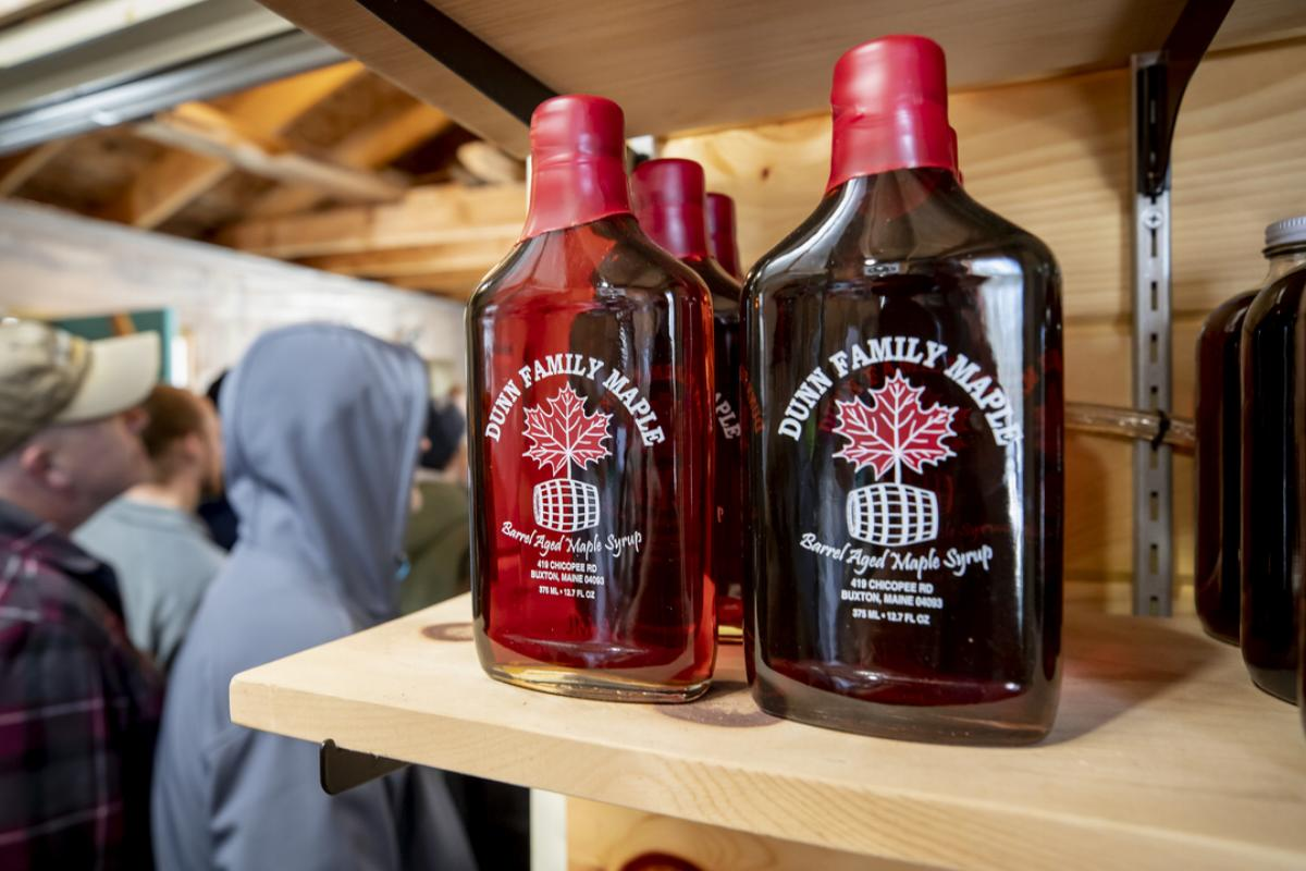 Barrel aged maple syrup sits on wooden shelves during Maple Sunday at Dunn Family Maple.