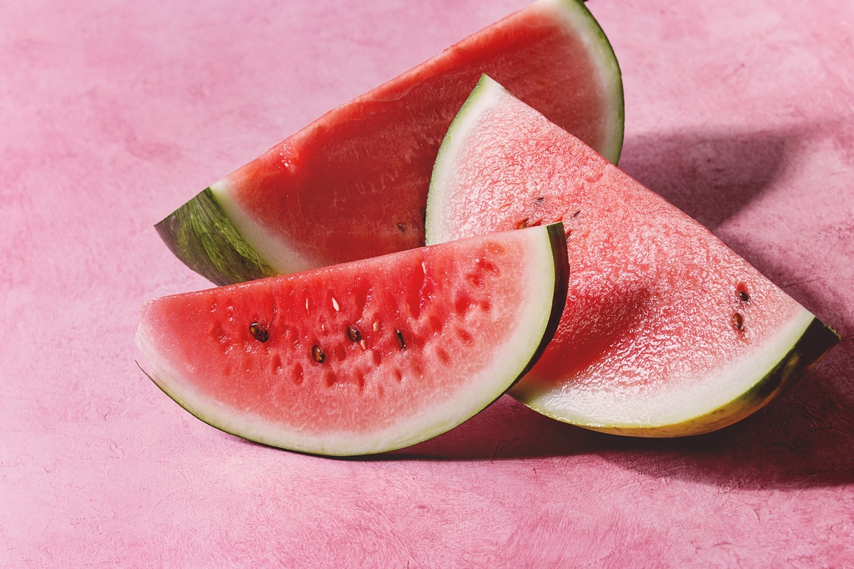 Ripe sliced watermelon sits against a pink texture background.