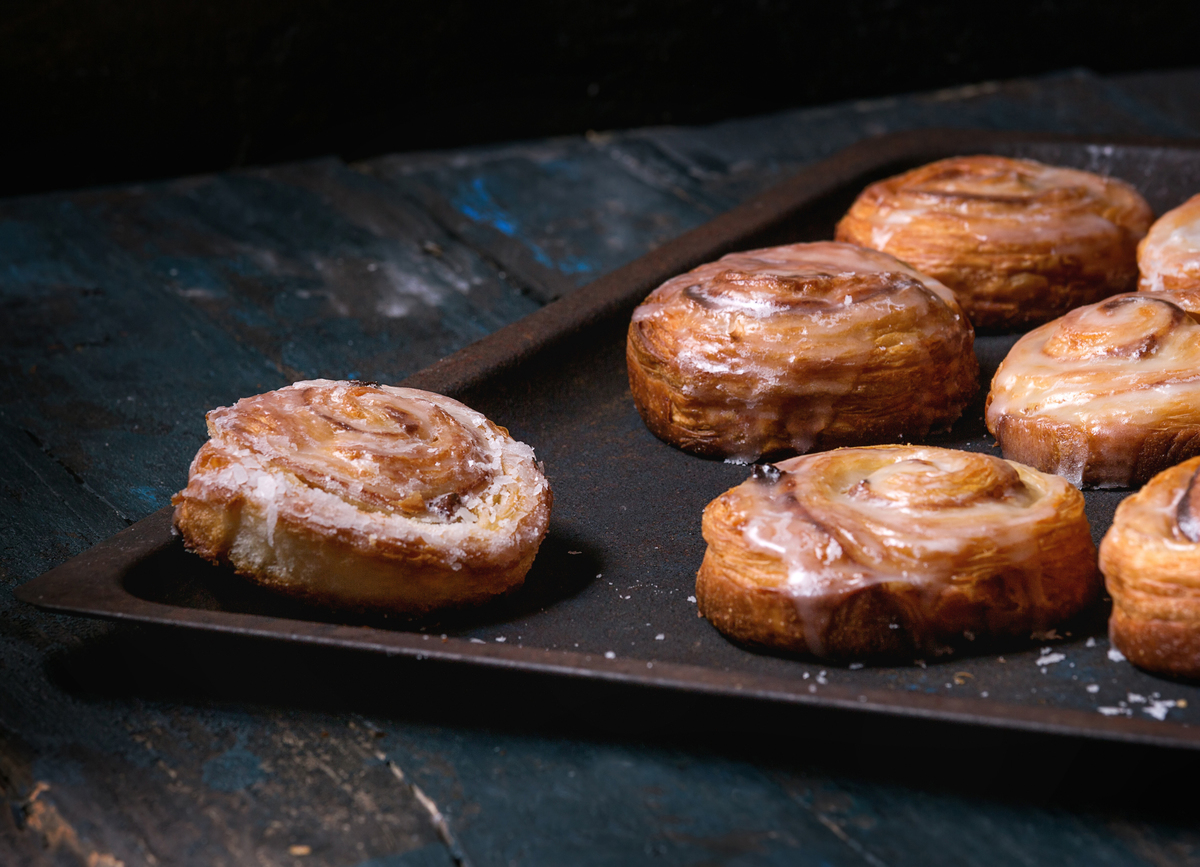 Homemade glazed puff pastry cinnamon rolls with custard and raisins are on an oven tray over old dark blue wood.