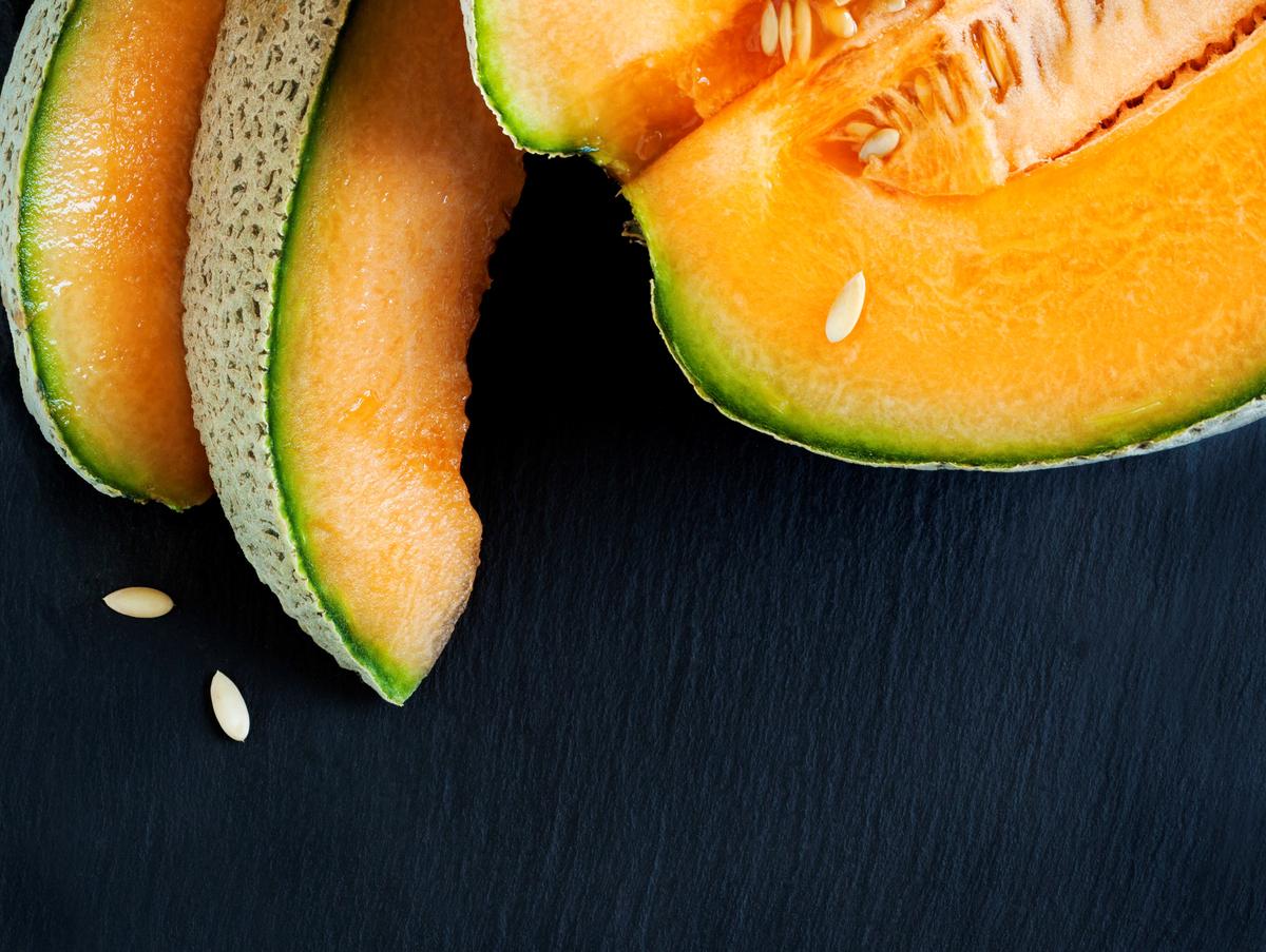 Cantaloupe melon slices lie against a dark blue background.