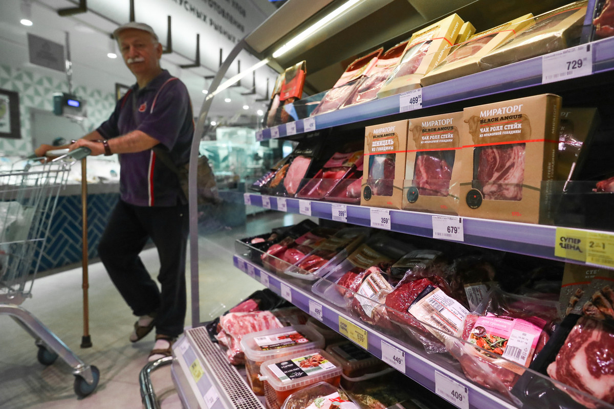 Man passes meat products for sale at a Perekrestok grocery store.