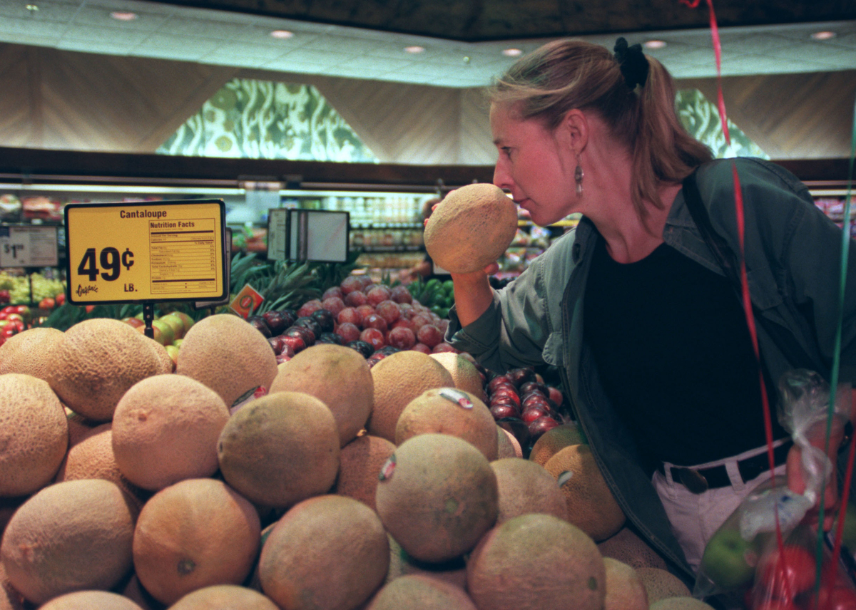 A customer chooses a cantaloupe from a grocery store.