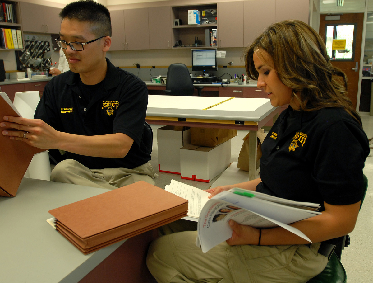 Sheriff and criminalist mull over the files of a cold case.