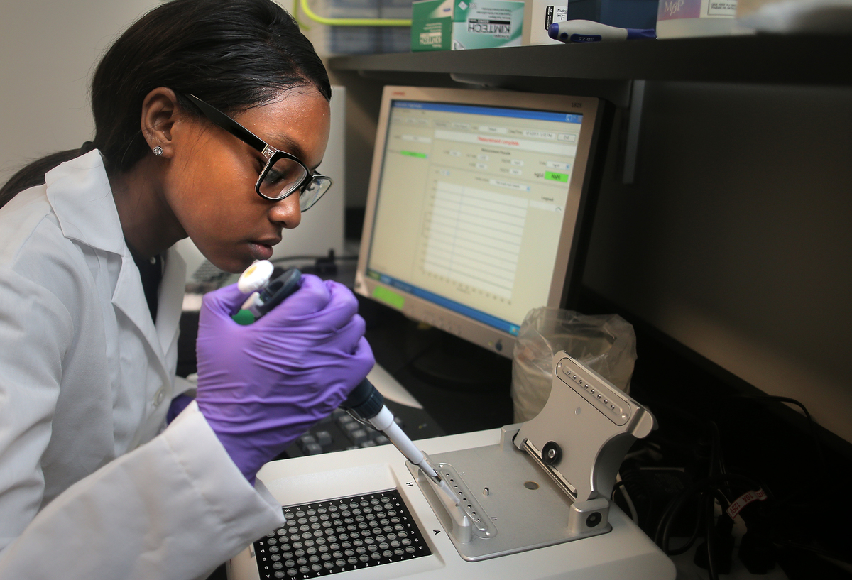 A woman works on quantifying DNA samples on a spectrophotometer.