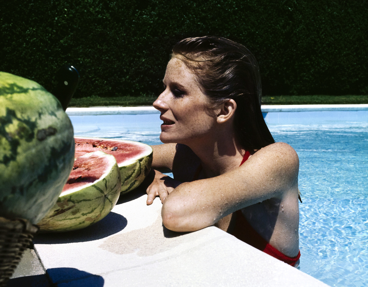Alexandra Cushing rests at the edge of her Southampton, New York pool with a sliced watermelon.