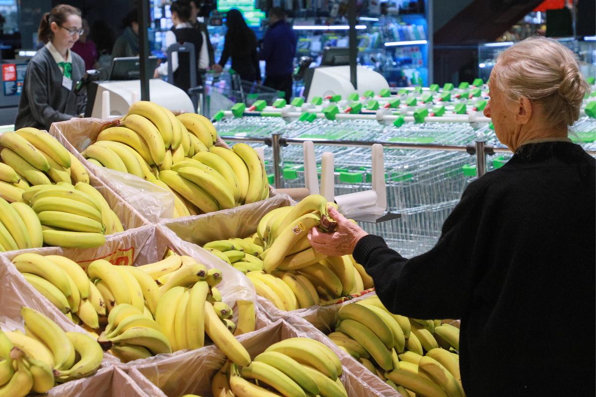 A customer chooses bananas at a Perekrestok grocery store.