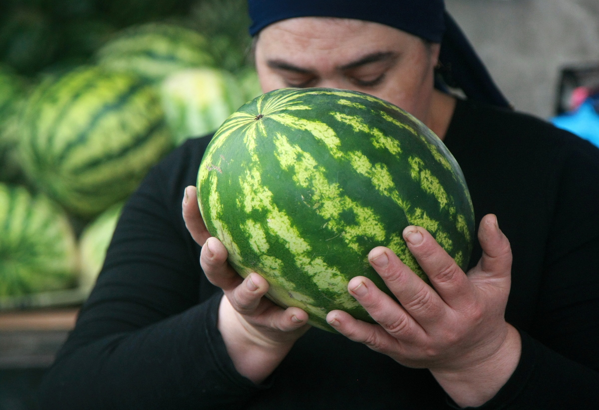 A person holds a watermelon on sale at a market.