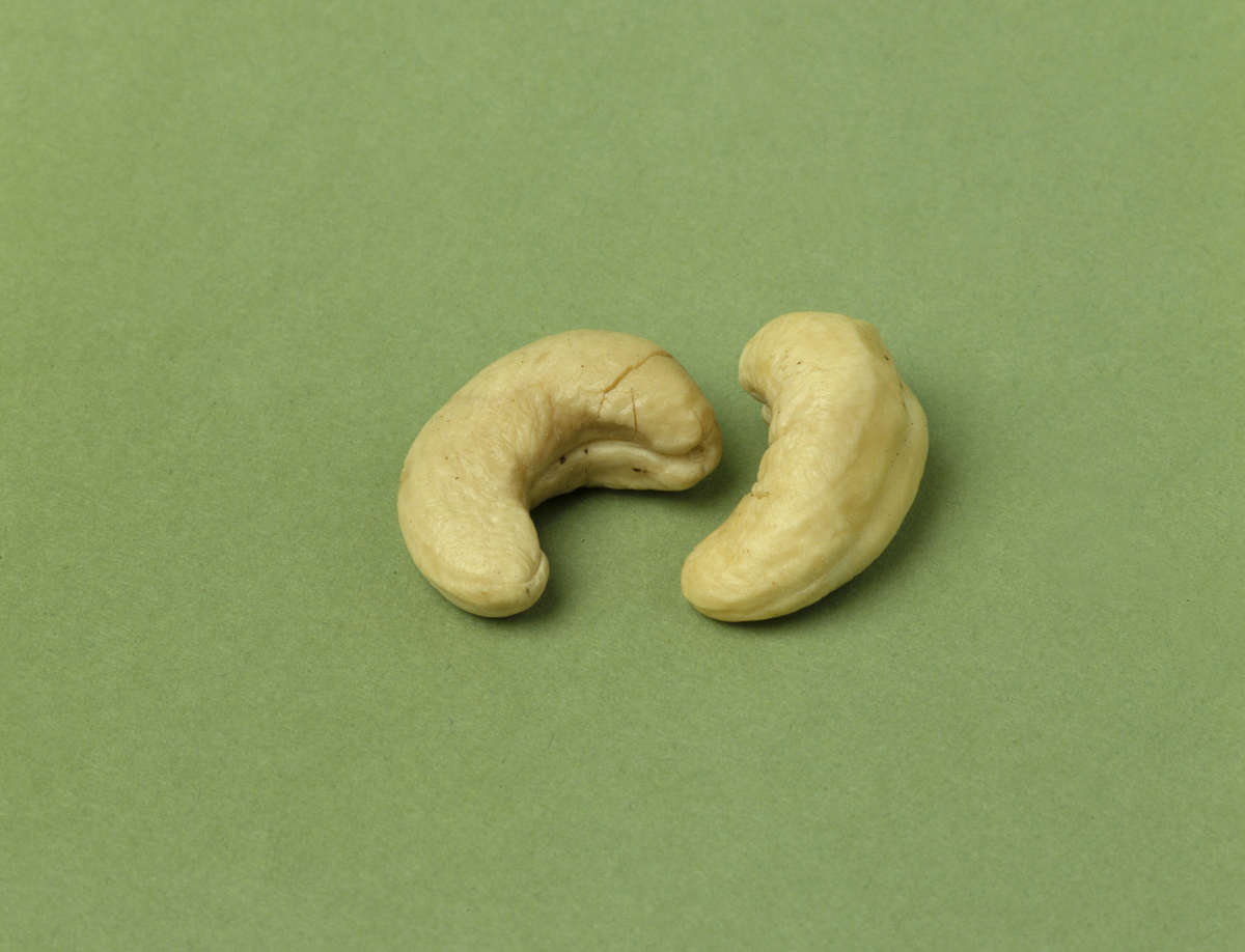 Two cashew nuts lay against a green background.