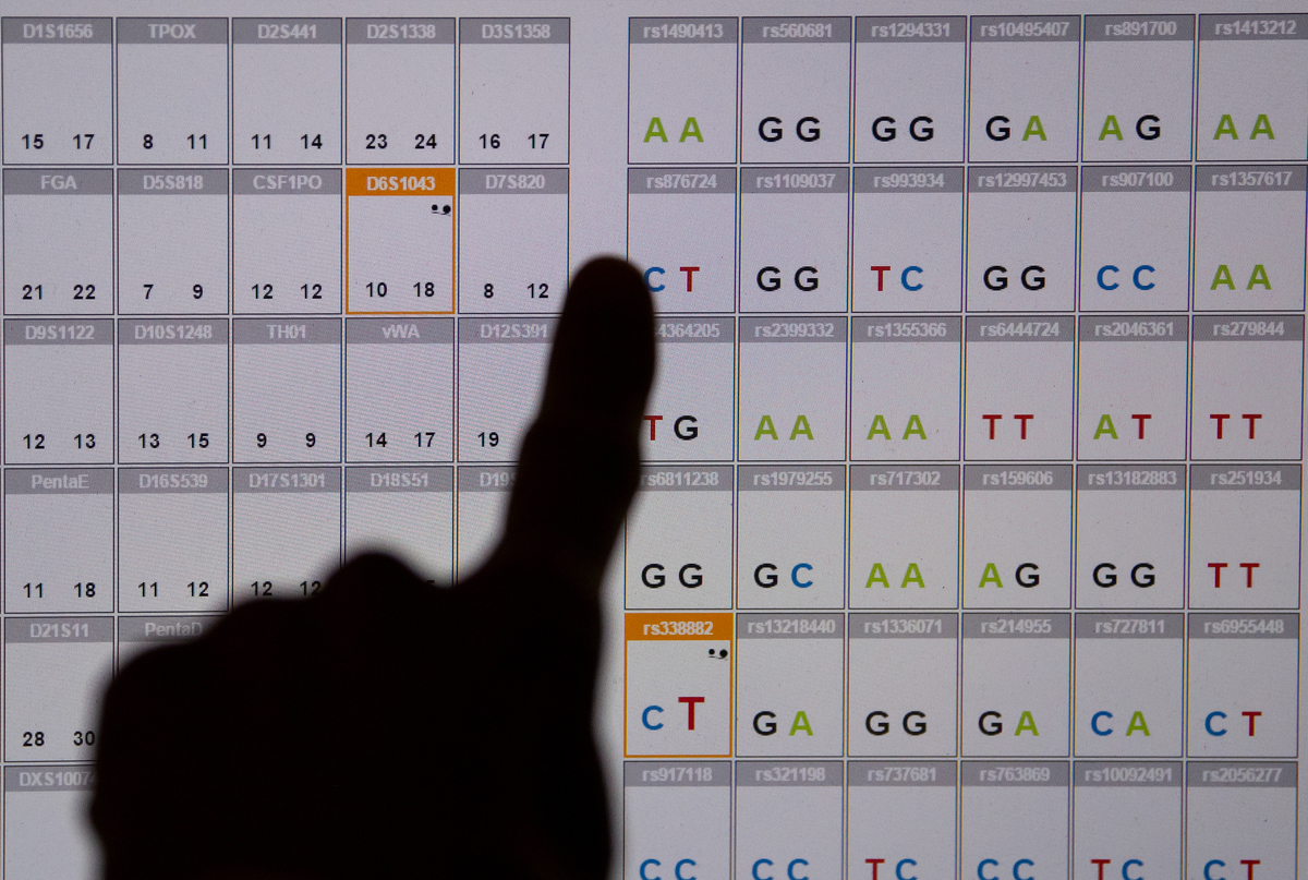 A scientist points at a DNA sequence on a monitor.