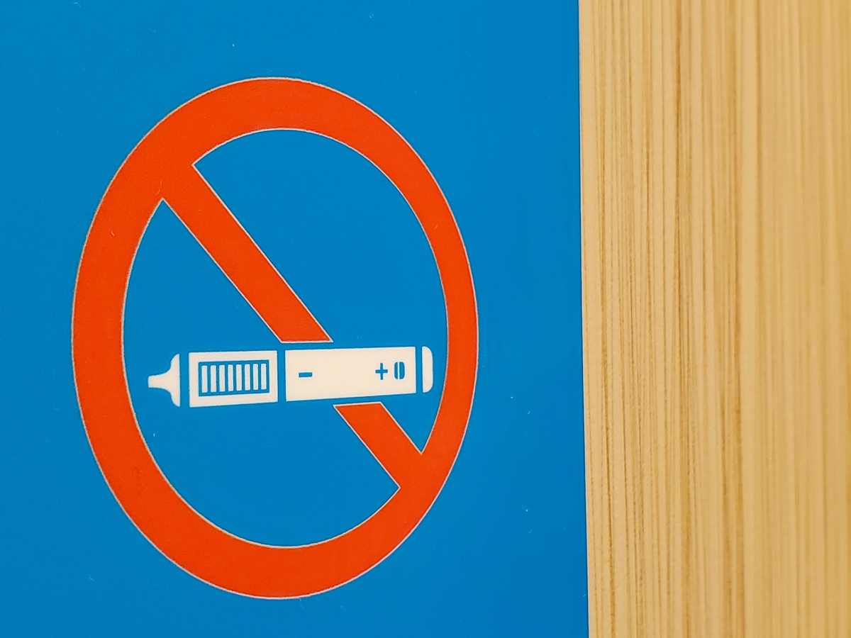 A No Vaping sign is seen near a light wooden wall surface, with stylized image of a vaping device or e-cigarette crossed out with a red circle.