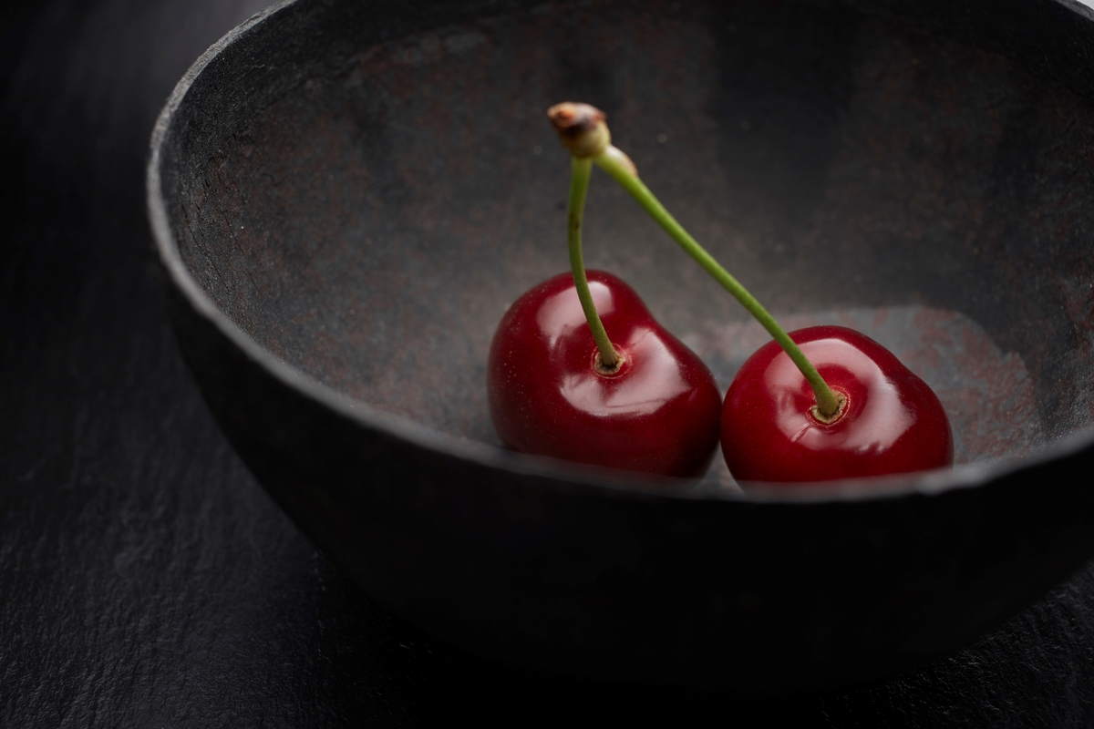 Two cherries sit in a black bowl against a dark background.