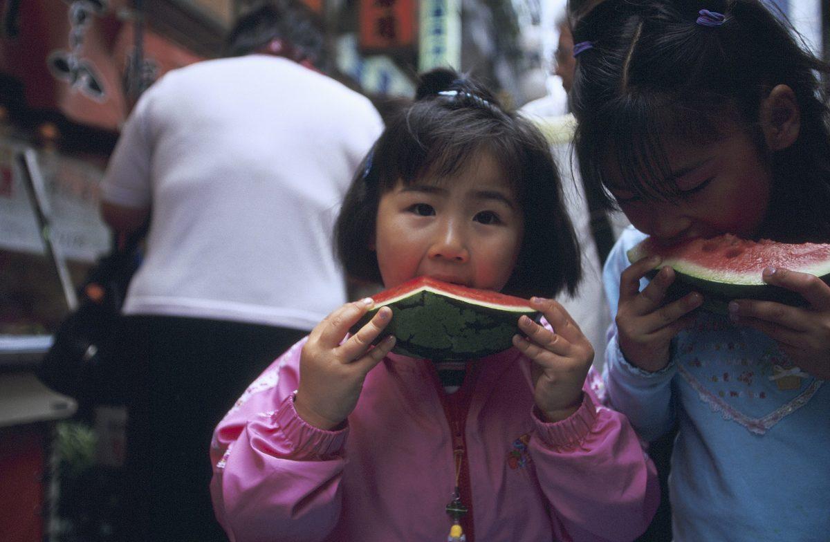 Girls eat watermelon at Ueno market in Tokyo, Japan