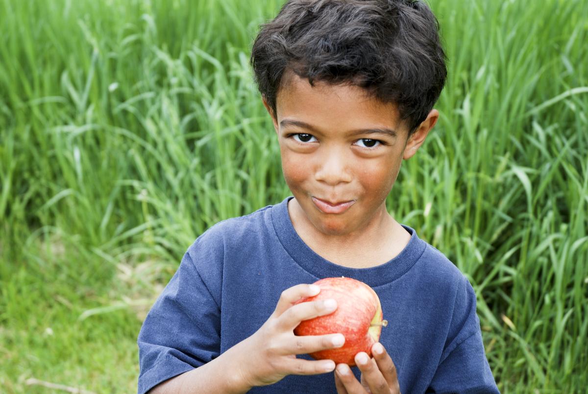 A boy eats an apple.